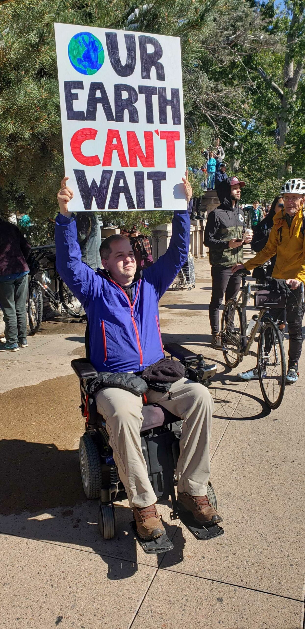 "Man (Councilman Chris Hinds) in wheelchair in khakis and purple jacket hold sign above his head that reads: ""Our Earth Can't Wait"""