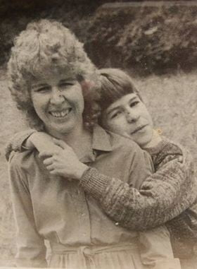 black and white photo of a woman being hugged over the shoulders by a young boy. Mother and son photo