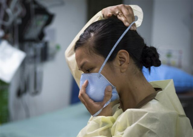 Female medical professional in emergency gear donning mask
